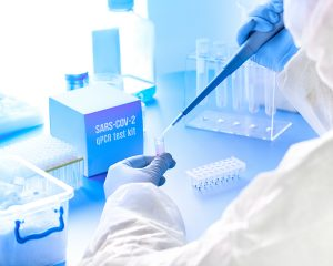Products and Services - SARS-COV-2 pcr diagnostics kit. Epidemiologist in protective suit, mask and glasses mixes reaction to detect virus in patients samples. PCR detects 2019-nCoV virus causing Covid-19 pneumonia.
