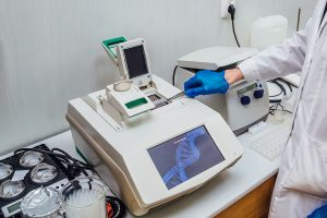 Real Time PCR Training - Scientist with gloved hand putting DNA sample into real-time PCR-cycler.